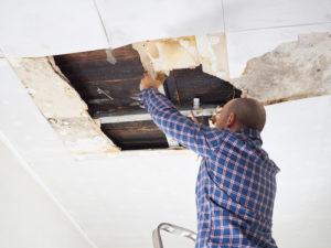 man fixing the ceiling - water damage restoration Irvine